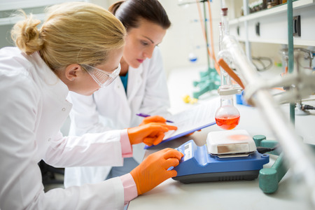 Foto de Female technicians adjusting measuring instrument in laboratory - Imagen libre de derechos
