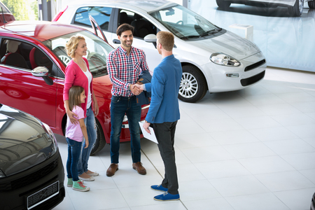 Photo pour car salesman showing new vehicle to family customers - image libre de droit