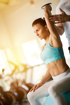 Foto de Woman doing  lifting dumbbells exercises with personal trainer - Imagen libre de derechos