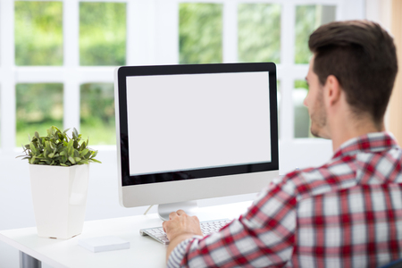 Photo for Young man looking at computer screen at home office - Royalty Free Image