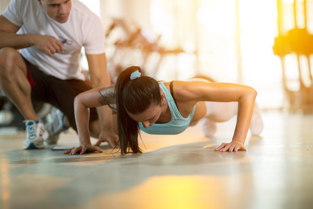 Photo pour Gym woman doing push ups with assisting her personal trainer - image libre de droit