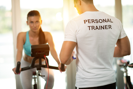 Foto de Personal trainer at the gym with client on bike - Imagen libre de derechos
