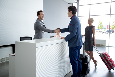 Foto de Man and receptionist handshake at reception hall - Imagen libre de derechos