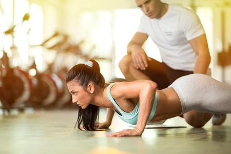 Foto de Personal trainer working with his client in gym - Imagen libre de derechos