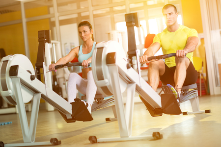 Foto de Fit  couple on row machine in gym, sport, fitness, lifestyle, and people concept - Imagen libre de derechos