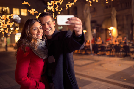 Foto de happy moments together. Happy young loving couple making selfie and smiling while standing Christmas background - Imagen libre de derechos