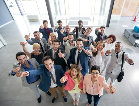 Foto de Portrait of thumb up smiling business people - Imagen libre de derechos