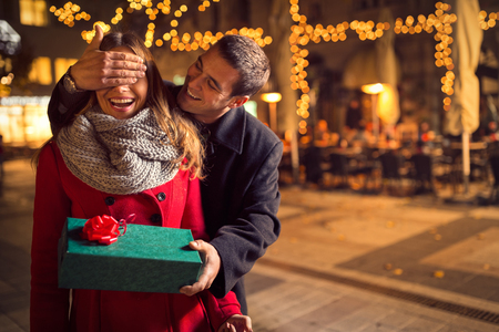 Photo pour Man  keeps his girlfriend eyes covered while  she giving a gift , romantic surprise for Christmas - image libre de droit