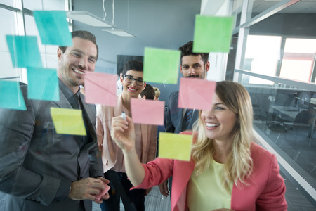 Photo pour Smiling modern partners looking at sticky notes - image libre de droit