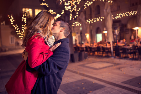 Foto de Young affectionate couple kissing tenderly on Christmas street - Imagen libre de derechos