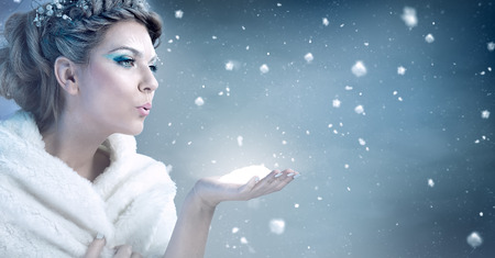 Foto de Winter woman  blowing snow over blue background - snow queen - Imagen libre de derechos