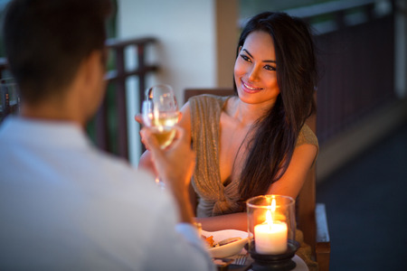 Foto de young couple with a romantic dinner with candles on tropical balcony - Imagen libre de derechos