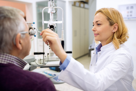 Photo pour Young female eye doctor determines eyes diopter using instruments in consulting room - image libre de droit