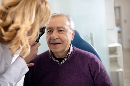 Photo pour Senior looks in instrument for checking eyes at ophthalmologist - image libre de droit