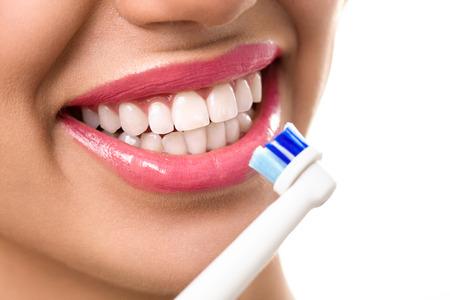 Foto de Close up of perfect and healthy teeth with electric toothbrush - Imagen libre de derechos