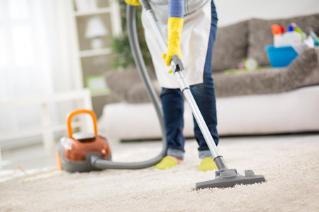 Photo pour Housewife from cleaning service cleans carpet with vacuum cleaner - image libre de droit