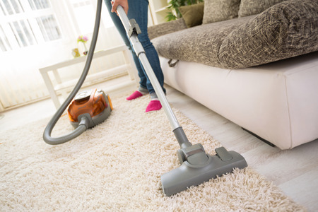 Photo pour Cleaning carpet with vacuum cleaner in living room - image libre de droit