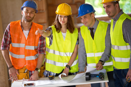 Photo pour Group of architects agreeing about schedule on construction site - image libre de droit