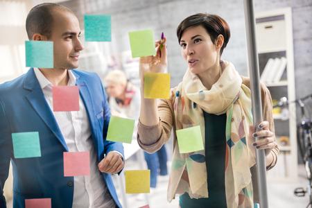 Foto de Designer discus about artistic plan with colleague in workplace - Imagen libre de derechos