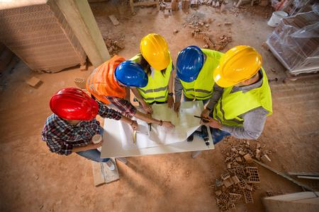 Photo pour Top view of construction team with colorful hard hat on building construction - image libre de droit