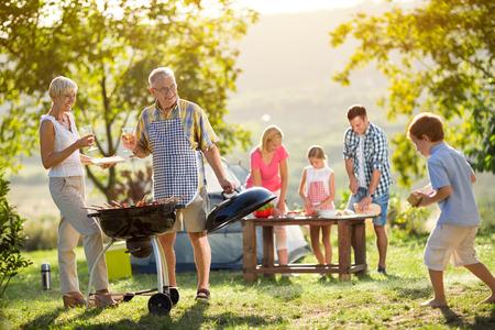 Foto de Happy family camping and cooking bbq - Imagen libre de derechos
