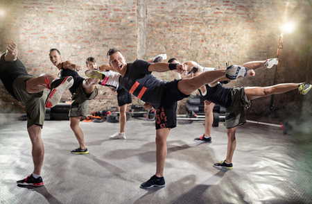 Photo for Group of young people  doing kick box exercise, expressing aggression - Royalty Free Image