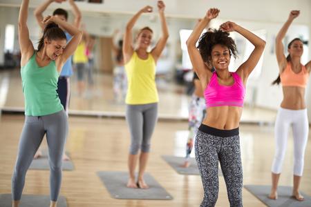 Foto de Attractive cheerful women dance at gym in colorful sportswear - Imagen libre de derechos