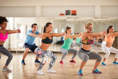 Foto de Fitness group doing exercises for shaping breech on fitness class - Imagen libre de derechos