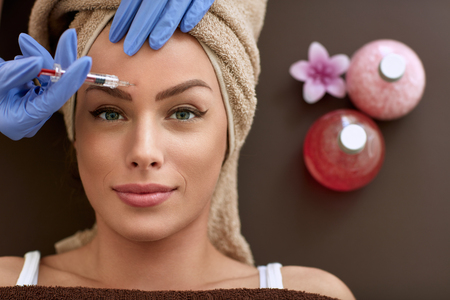Photo pour Beauty woman giving botox injections. botox, cosmetic treatments, wrinkle removal, Botox injections - image libre de droit