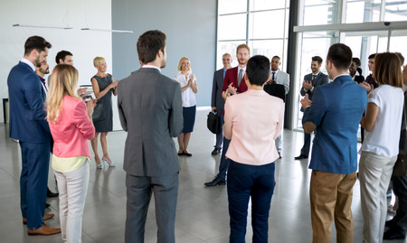 Photo for young leader standing in front of his partners who applauding - Royalty Free Image