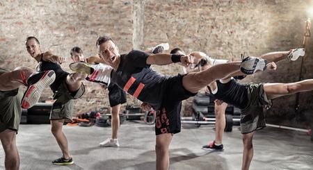 Foto de Group of young people  doing kick box exercise, expressing aggression - Imagen libre de derechos