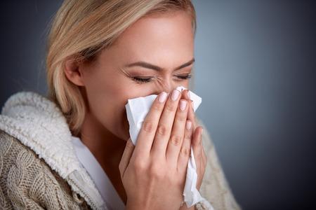 Photo pour Cold woman holding handkerchieif blowing nose - image libre de droit