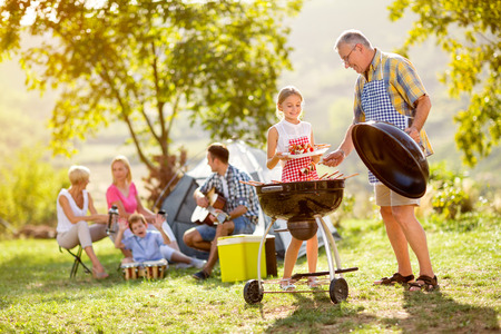 Foto de granddaughter making barbecue with grandfather on camping - Imagen libre de derechos