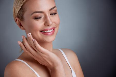 Photo pour Nice middle aged woman  applying face cream, joyfully smiling - image libre de droit