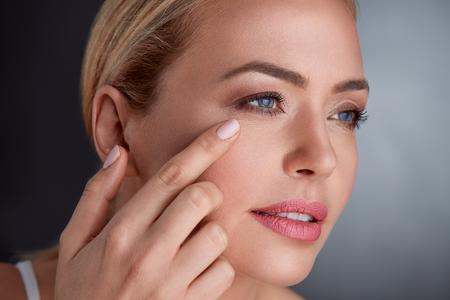 Photo pour middle age woman looking skin on  her face - image libre de droit