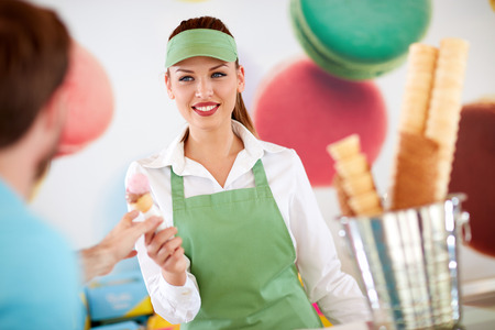 Photo pour Beautiful female worker in confectionery giving ice cream to customer - image libre de droit