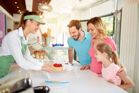 Photo pour Saleswoman in bakery packing fruit cake with strawberry for family - image libre de droit