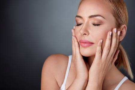 Foto de Beautiful middle aged woman touching her face,  skincare , perfect skin - Imagen libre de derechos