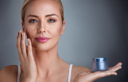 Photo pour Beautiful nourished woman holding cream for her skin - image libre de droit