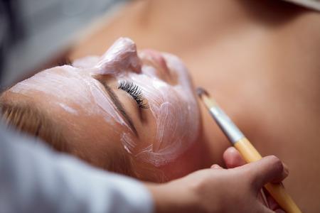 Photo pour Beautiful young woman having a facial cosmetic treatment. - image libre de droit