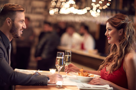 Foto de Female and male enjoy at restaurant with dinner together - Imagen libre de derechos