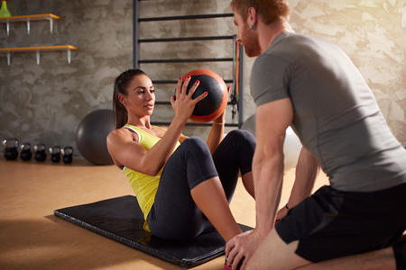 Photo for Girl exercises abs muscles using ball in fitness center - Royalty Free Image