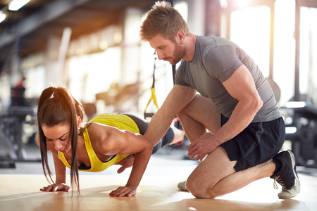 Photo for Fitness instructor on job with female athlete in gym - Royalty Free Image