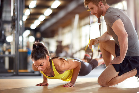 Foto de Fitness instructor with girl on training in fitness center - Imagen libre de derechos