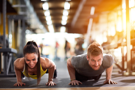 Foto de Couple doing pushups at training in gym - Imagen libre de derechos