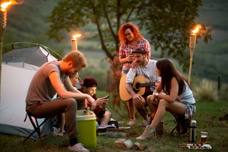 Photo pour Group of young people at night in campground look at photos on mobile - image libre de droit