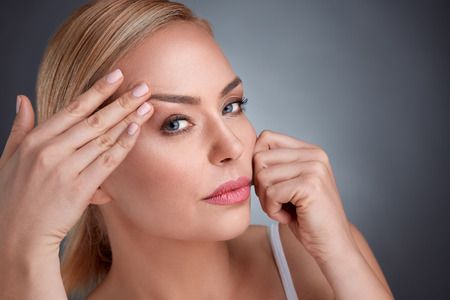 Foto de middle aged women try to see how to look that there are no wrinkles - Imagen libre de derechos