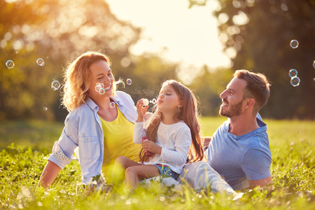 Photo for Family with children blow soap bubbles outdoor - Royalty Free Image