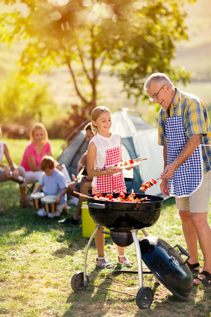 Photo pour smiling grandfather and granddaughter grilling barbecue for family - image libre de droit