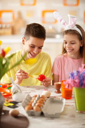 Photo pour Boy and girl painting red Easter egg in kitchen - image libre de droit